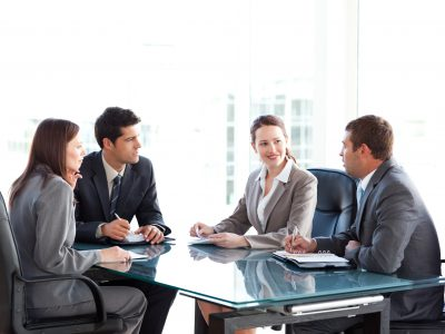Businessmen and businesswomen talking during a meeting sitting at a table